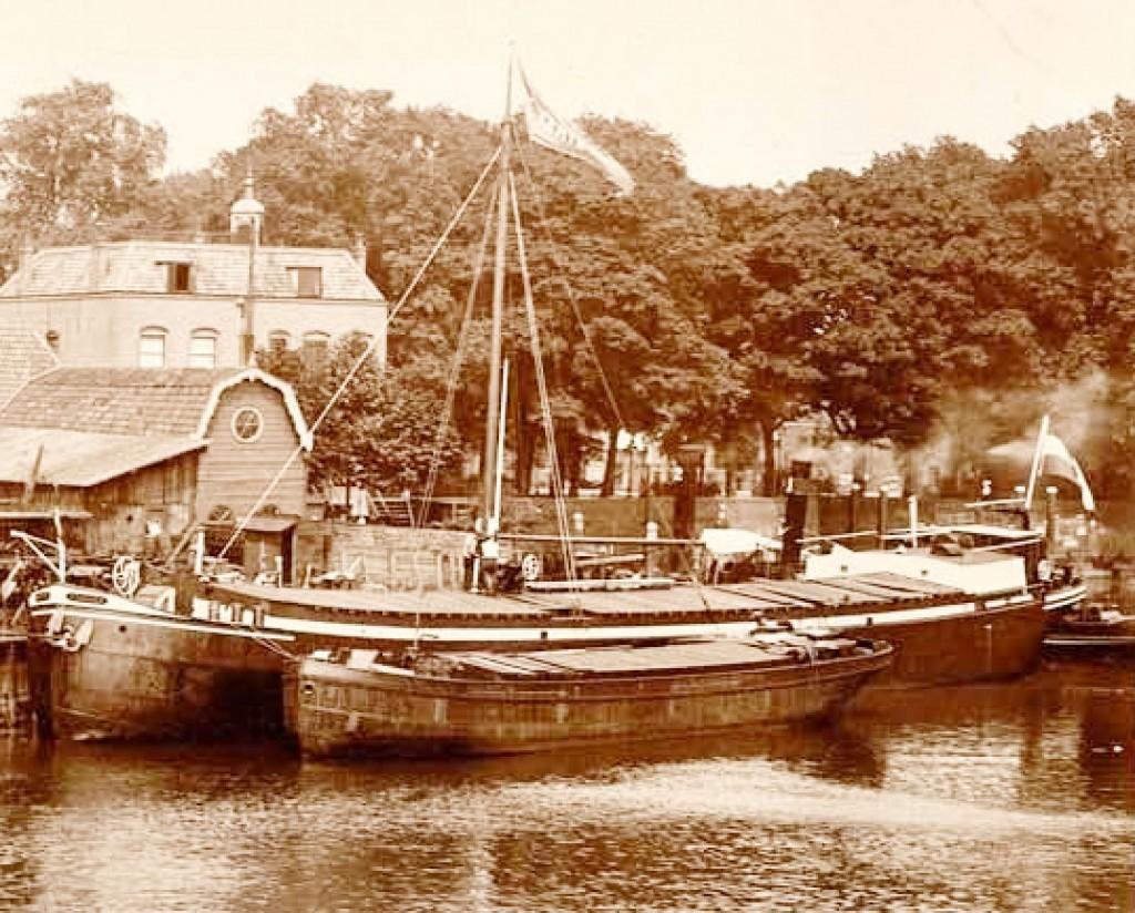 Deze foto is genomen vanaf de overzijde van de rivier. Op de plek van de houten schuur is rond 1950 de schoorsteen gebouwd voorde kaarsenfabriek. Voor de bomen van het parkje aan het Buurtje ziet u het verlengde van de kademuur die begon bij deMallegatsluis.