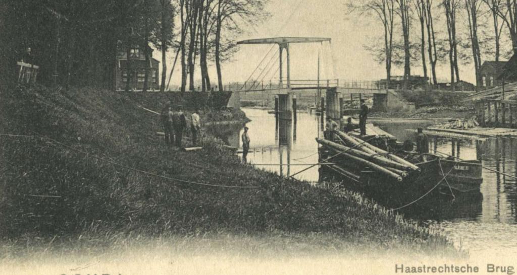 Foto van de oever aan de stadskant bij de in 1957 afgebroken oude Haastrechtsebrug toen de berm onder aan de dijk nog breed was .